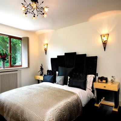 Темное изголовье на фоне сбелых стен в спальне в стиле арт-деко