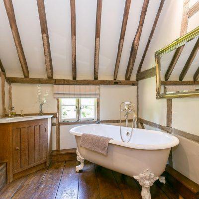 Угловое расположение ванной в викторианском стиле на мансарде