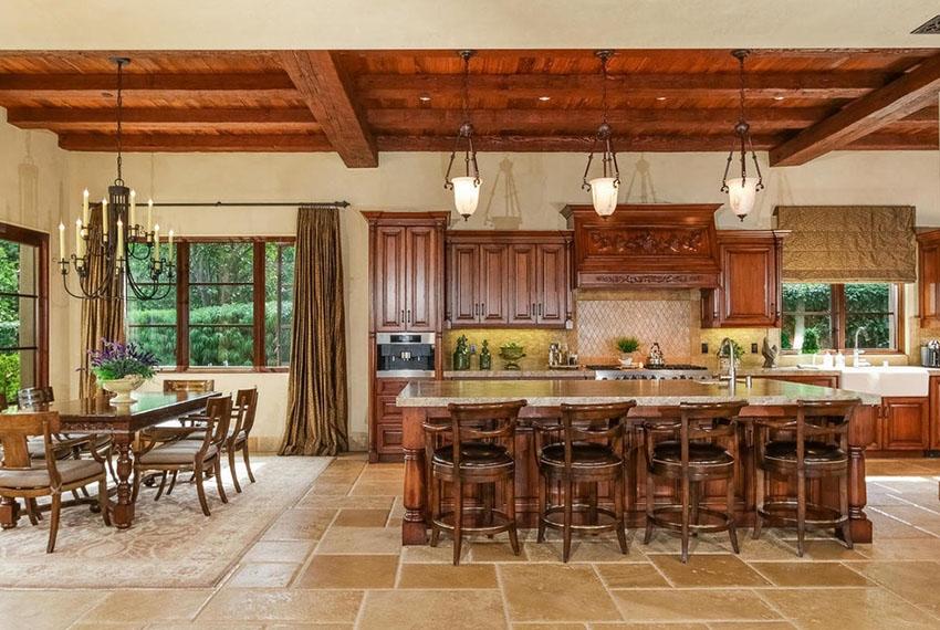 На просторной кухне стоит сделать несколько источников света, дополнив кованые люстры незаметной встроенной подсветкой