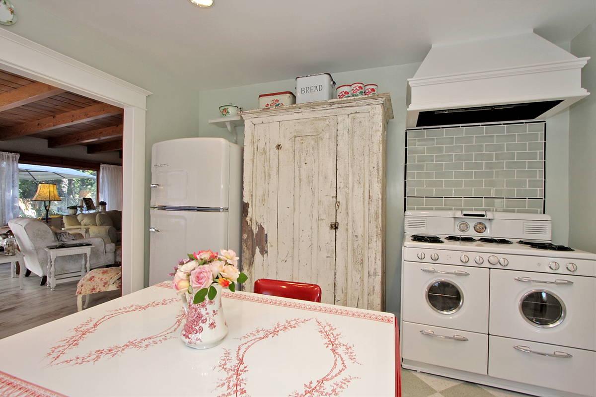 Потертая и обшарпанная мебель в совокупности со стильной техникой создают винтажный и отчасти деревенский стиль кухни