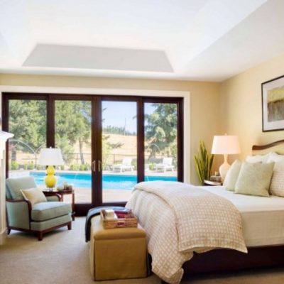 Королевская кровать в спальне американского стиля с окнами