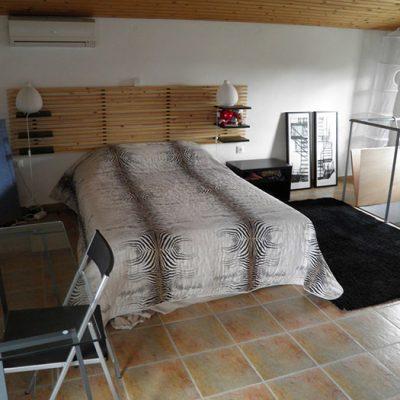 Просторная спальная комната с картиной на фото образце лофт стиля