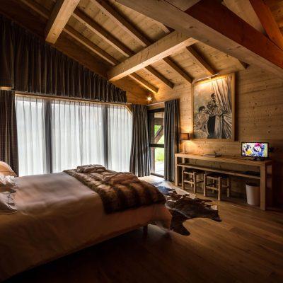 Спальня шале стиля со шторами на мансарде