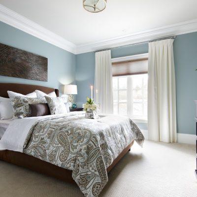 Кровать в спальне с картиной в интерьере
