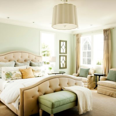 Кровать в спальне с картиной в интерьере американского стиля на фото