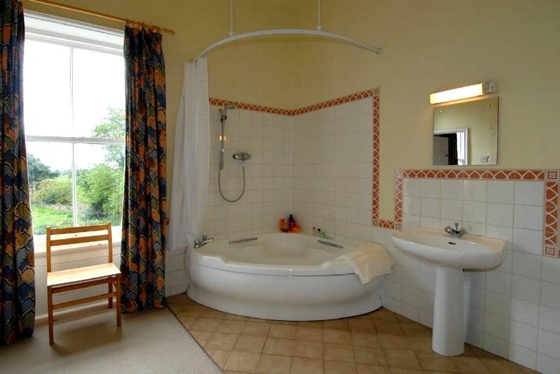 Угловая ванная в интерьере ванной комнаты