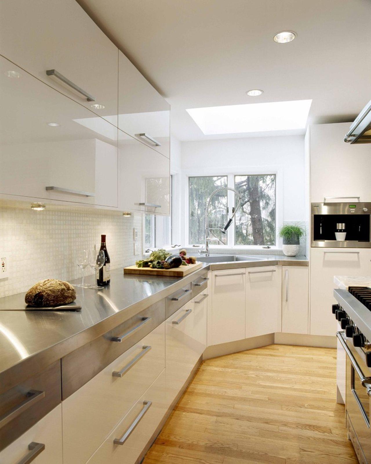Кухня с зеркальным белым фасадом, дополненная хромированной столешницей и фурнитурой