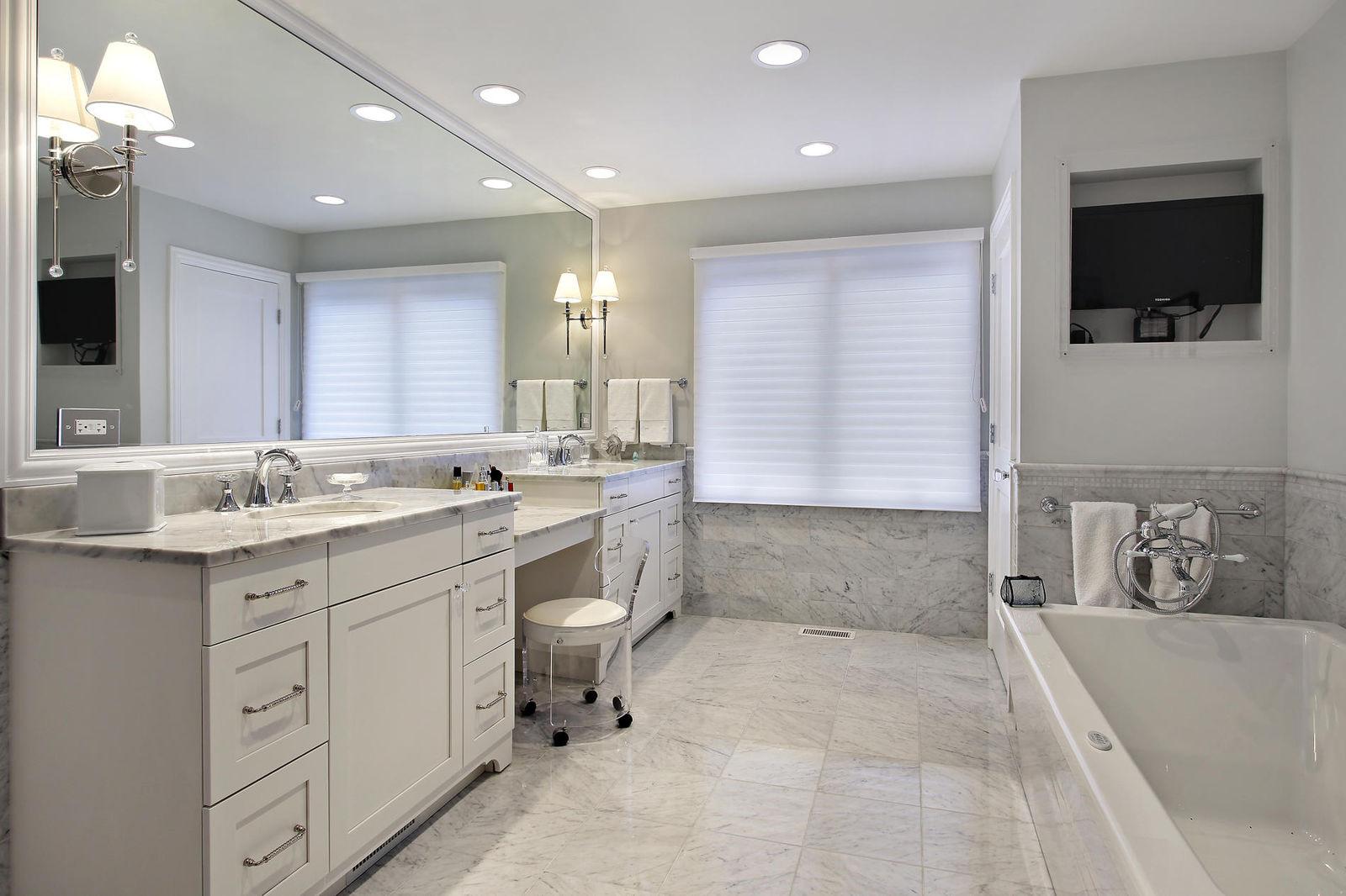 При желании можно совместить ванную с кабинетом, вписав в привычный интерьер рабочий стол, стулья, плазму