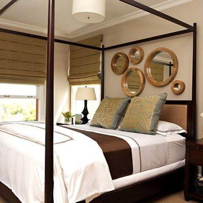 Круглые зеркала в спальне над кроватью