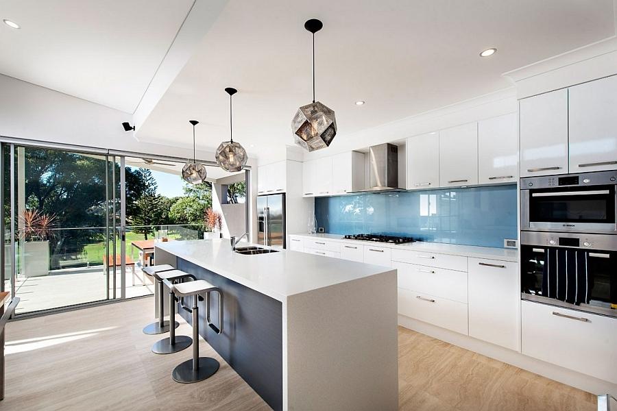 На просторной кухне хорошо смотрятся одинаковые люстры, повешенные в ряд