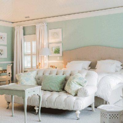 Кровать в спальне с картиной в интерьере американского стиля