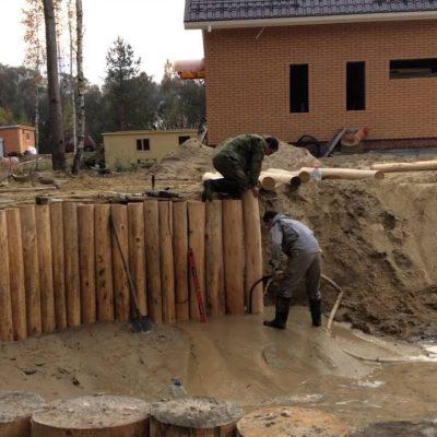 Установка подпорной стенки из бревен